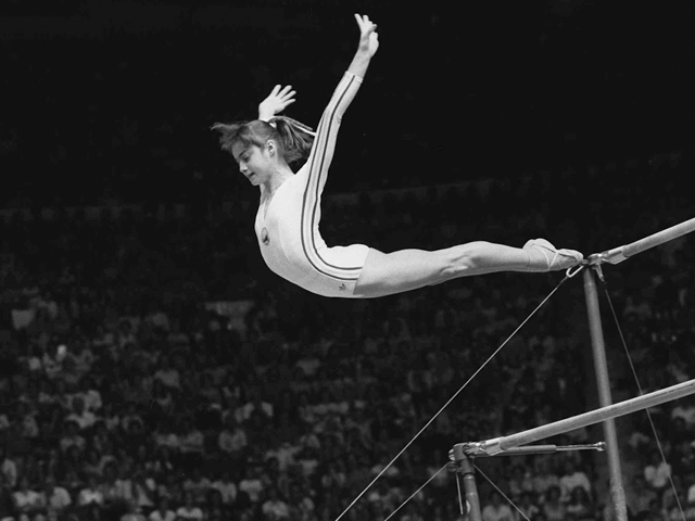 Nadia Comaneci, of Romania, dismounts from the uneven parallel bars at the Olympic Games in Montreal